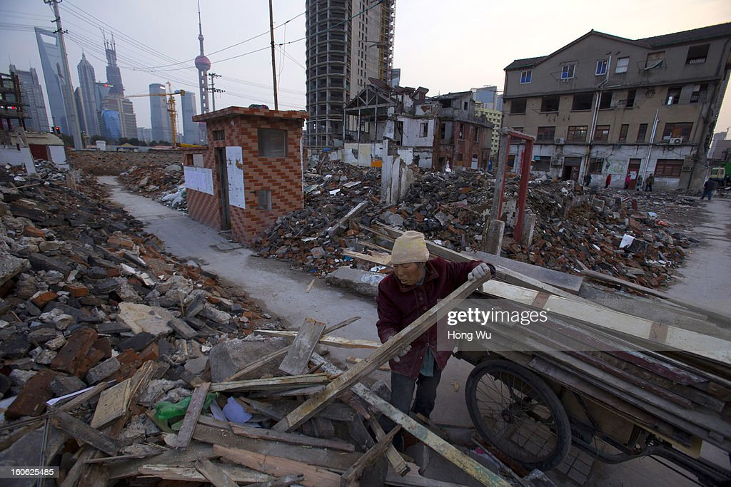 A garbage picker collects wood at a demolition area on February 2, 2013 in Shanghai, China.