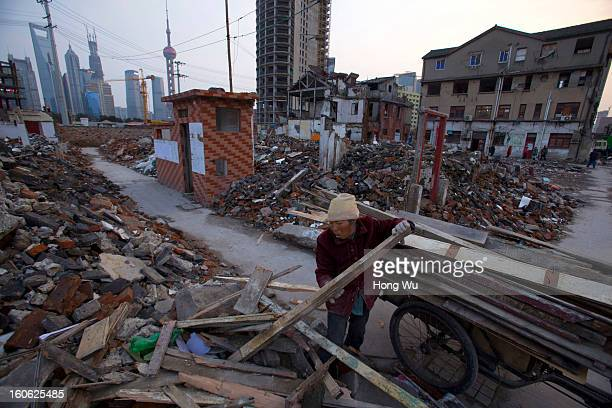 A garbage picker collects wood at a demolition area on February 2 2013 in Shanghai China