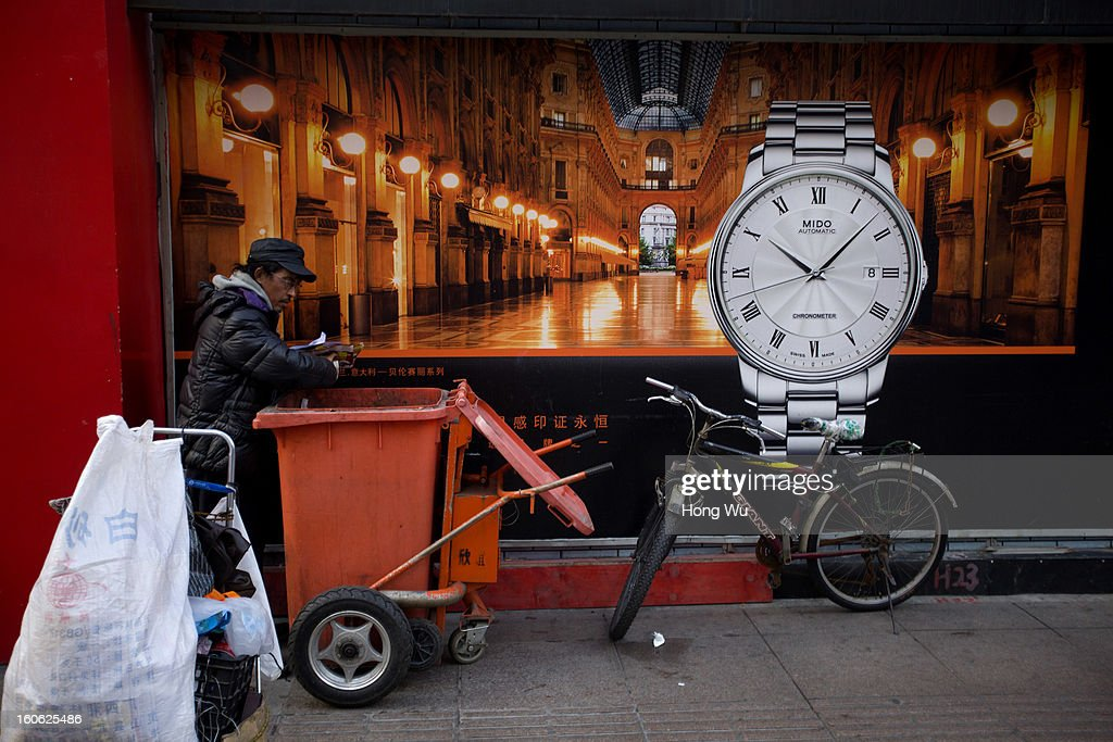 A garbage picker searches useful thing beside a clock billboard on February 3, 2013 in Shanghai, China.