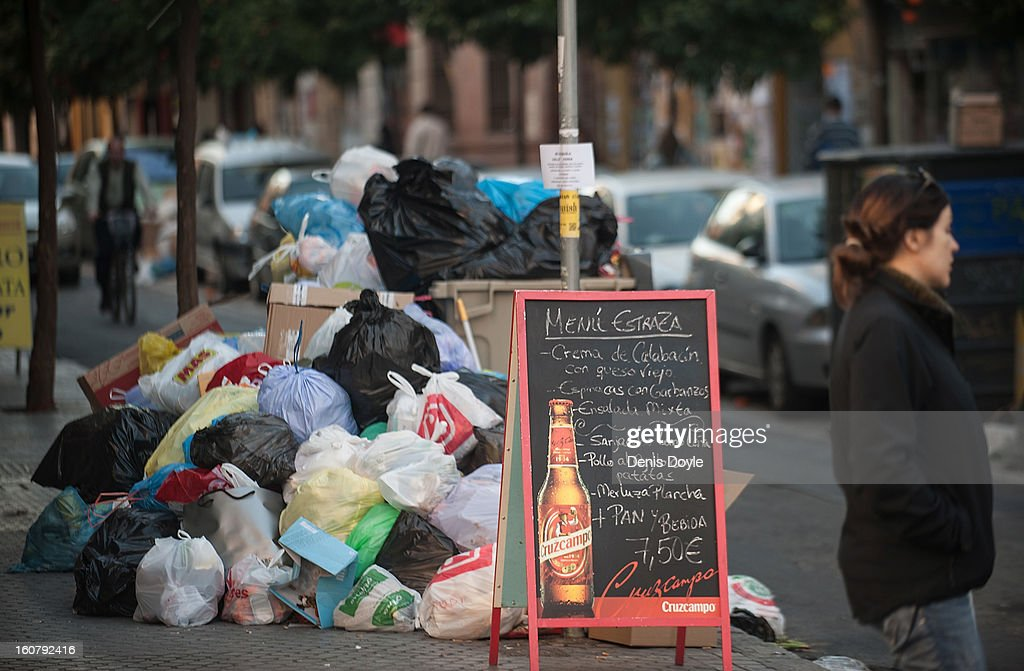 Garbage piles up on the street beside a bar sign displaying lunch prices during the ninth day of the Seville waste disposal strike on February 5, 2013 in Seville, Spain. Workers are striking over demands they take a 5% pay cut and extend their working week to 37.5 hours.