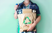 Woman's hands holding recyclable garbage - plastic bottle and cardboard boxes. Recycling, environment and ecology concept.