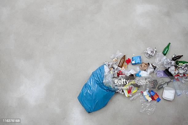 Garbage spilling from plastic bag on gray background