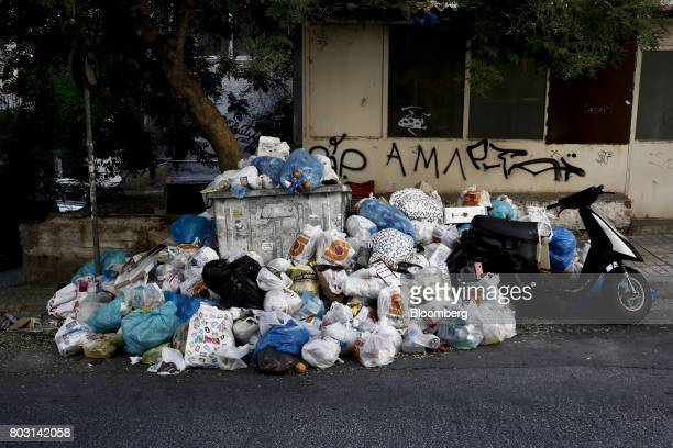 Garbage surrounds a refuse bin on a city sidewalk during a refuse collection strike by municipal workers in Athens Greece on Wednesday June 28 2017...
