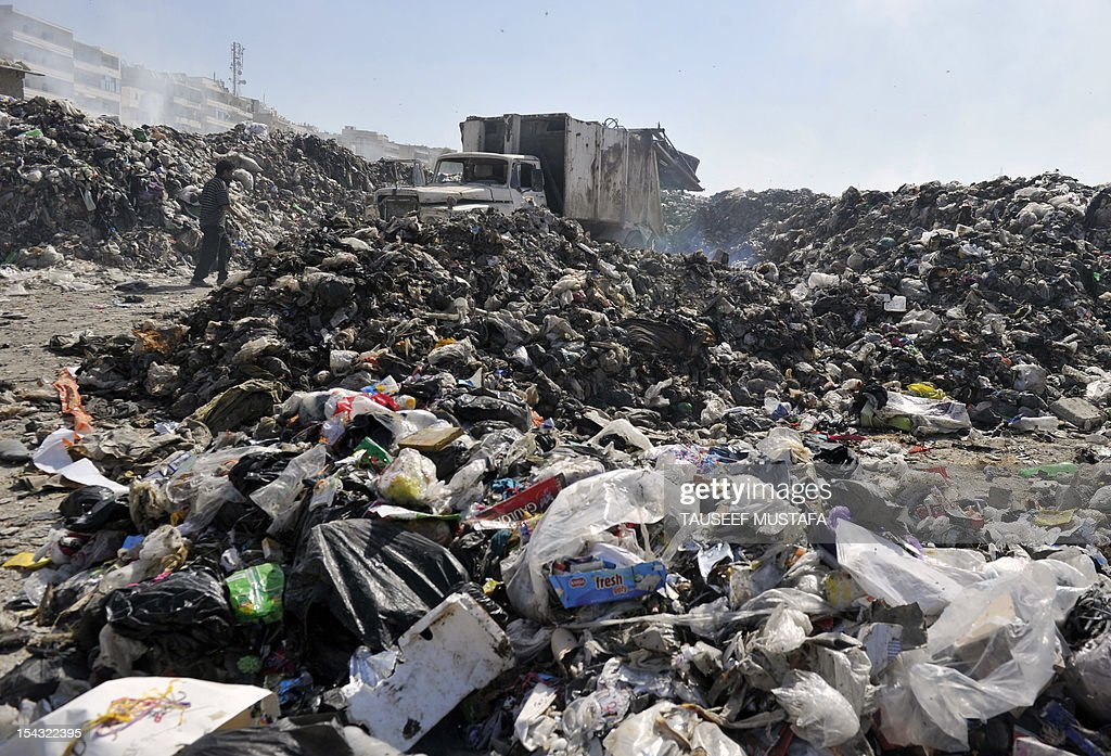 A garbage truck dumps its load in a dump near a hospital in the northern Syrian city of Aleppo on October 15, 2012. As the battle for the city rages, piles upon piles of rubbish, from rotting food to bloody bandages and other grisly medical waste, litter the streets swarming with flies.