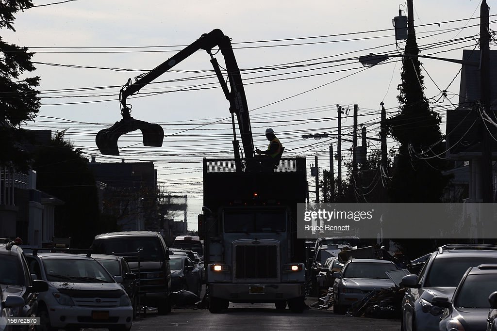 A garbage truck removes debris from Buffalo Avenue on November 20, 2012 in Long Beach, New York. More than three weeks after Superstorm Sandy hit the New York area, residents continue their restoration efforts in many affected areas on Long Island.