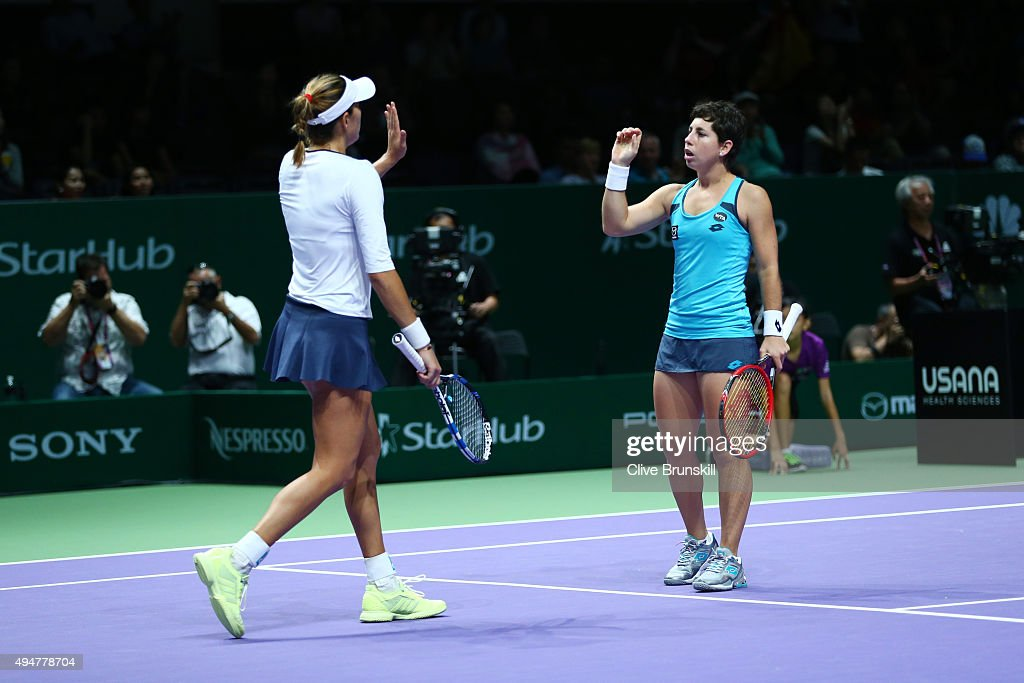 Garbine Muguruza and <a gi-track='captionPersonalityLinkClicked' href=/galleries/search?phrase=Carla+Suarez+Navarro&family=editorial&specificpeople=5294252 ng-click='$event.stopPropagation()'>Carla Suarez Navarro</a> of Spain celebrate match point against Hao-Ching Chan and Yung-Jan Chan of Chinese Taipei in a doubles round robin match during the BNP Paribas WTA Finals at Singapore Sports Hub on October 29, 2015 in Singapore.