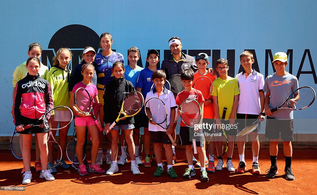 Garbine Muguruza and David Ferrer of Spain pose for a photograph with the children before holding a tennis clinic during day one of the Mutua Madrid Open tennis tournament at the Caja Magica on April 30, 2016 in Madrid, Spain. .
