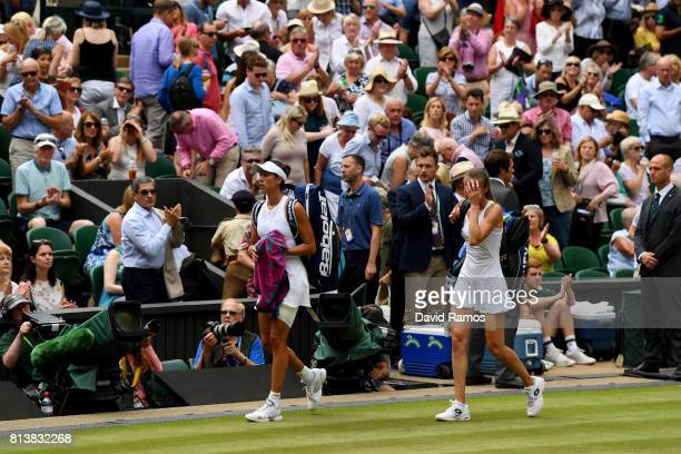 Garbine Muguruza of Spain and Magdalena Rybarikova of Slovakia walk off court after the Ladies Singles semi final match on day ten of the Wimbledon...