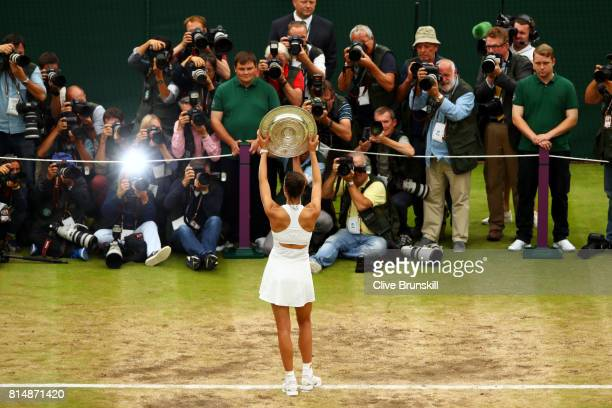 Garbine Muguruza of Spain celebrates victory with the trophy as she poses for photographers after the Ladies Singles final against Venus Williams of...