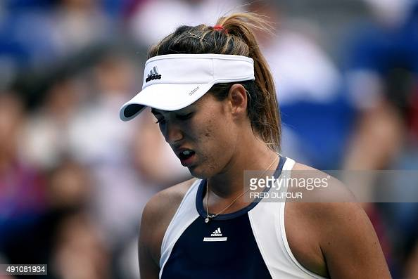 Garbine Muguruza of Spain gestures after retiring during the women's singles final against Venus Williams of the US at the Wuhan Open tennis...