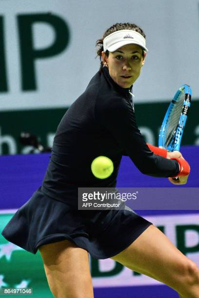 Garbine Muguruza of Spain hits a return against Jelena Ostapenko of Latvia during the WTA Finals tennis tournament Singapore on October 22 2017 / AFP...