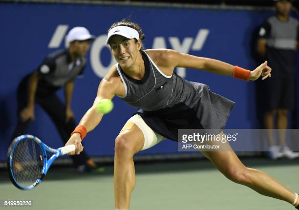 Garbine Muguruza of Spain hits a return against Monica Puig of Puerto Rico during their women's singles second round match at the Pan Pacific Open...