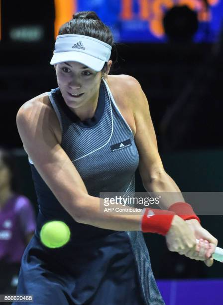 Garbine Muguruza of Spain hits a return against Venus Williams of the US during the WTA Finals tennis tournament in Singapore on October 26 2017 /...