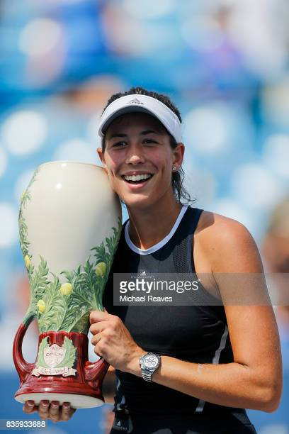 Garbine Muguruza of Spain holds up the trophy after defeating Simona Halep of Romania to win the women's final of the Western and Southern Open at...