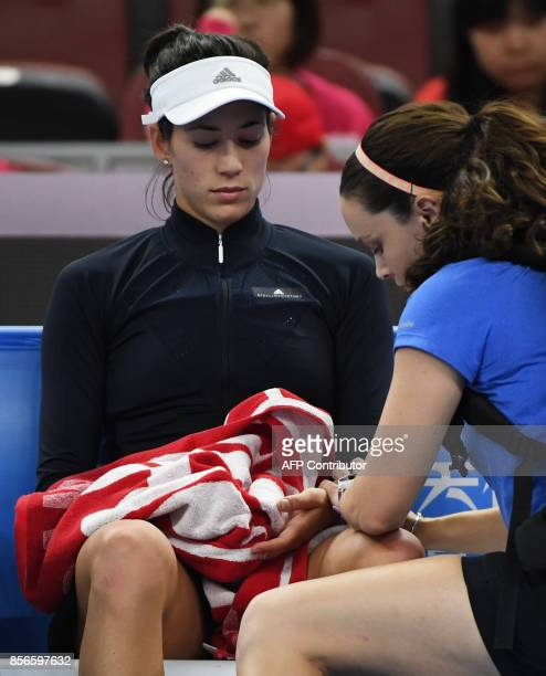 Garbine Muguruza of Spain is attended to by a trainer before retiring from her women's singles match against Barbora Strycova of the Czech Republic...