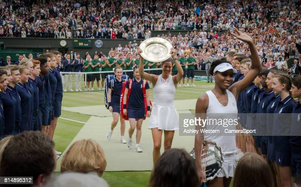 Garbine Muguruza of Spain leaves the court with the Venus Rosewater Dish after her victory over Venus Williams of United States in their Ladies'...