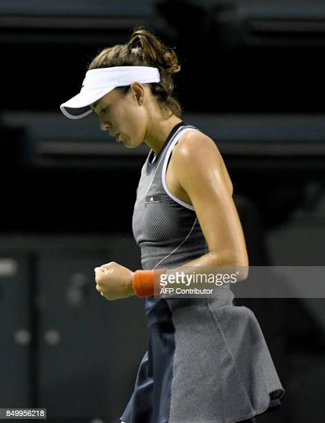 Garbine Muguruza of Spain reacts after winning a point against Monica Puig of Puerto Rico during their women's singles second round match at the Pan...