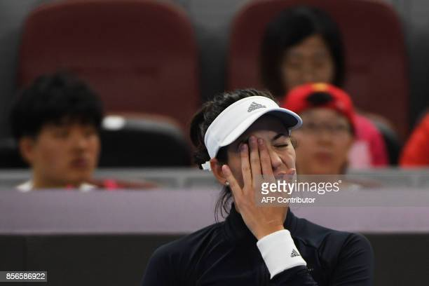 Garbine Muguruza of Spain reacts just before retiring from her women's singles match against Barbora Strycova of the Czech Republic at the China Open...