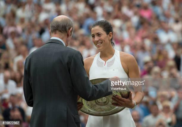 Garbine Muguruza of Spain receives the Venus Rosewater dish from HRH Duke of Kent after victory in the Ladies Singles final against Venus Williams of...