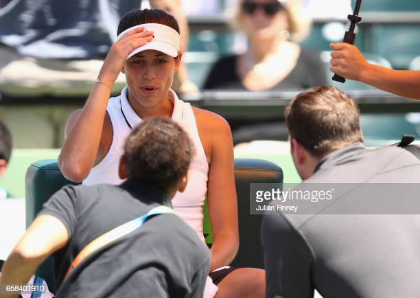 Garbine Muguruza of Spain receives treatment before pulling out in her match against Caroline Wozniacki of Denmark at Crandon Park Tennis Center on...