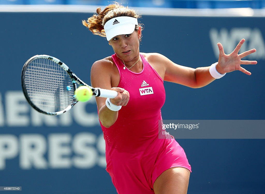 Garbine Muguruza of Spain returns a shot to Shuai Peng of China during the Connecticut Open at the Connecticut Tennis Center at Yale on August 20...
