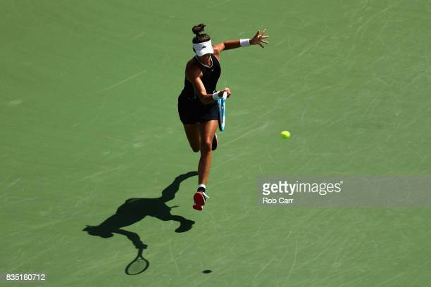 Garbine Muguruza of Spain returns a shot to Svetlana Kuznetsova of Russia during Day 7 of the Western and Southern Open at the Linder Family Tennis...