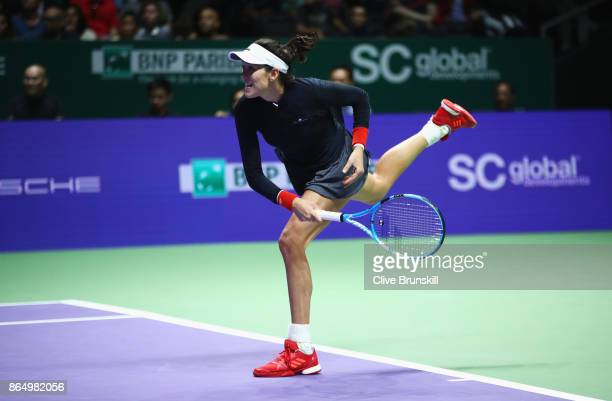 Garbine Muguruza of Spain serves in her singles match against Jelena Ostapenko of Latvia during day 1 of the BNP Paribas WTA Finals Singapore...