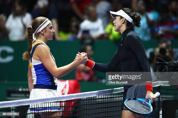 Garbine Muguruza of Spain shakes hands with Jelena Ostapenko of Latvia after her victory during day 1 of the BNP Paribas WTA Finals Singapore...