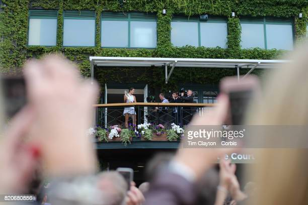 Garbine Muguruza of Spain shows her winner trophy to the crowd on the balcony of Centre court after her victory against against Venus Williams of The...
