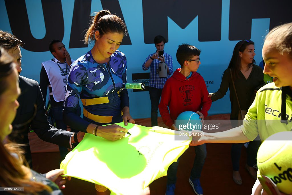 Garbine Muguruza of Spain signs autographs after a childrens tennis clinic during day one of the Mutua Madrid Open tennis tournament at the Caja Magica on April 30, 2016 in Madrid, Spain. .