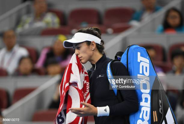 Garbine Muguruza of Spain walks off the court after retiring from her women's singles match against Barbora Strycova of the Czech Republic at the...