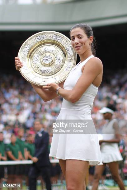 Garbine Muguruza of Spain with the winners trophy after victory in the Ladies Singles final as Venus Williams of The United States walks back to her...
