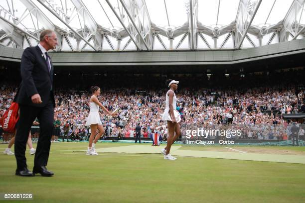 Garbine Muguruza of Spain with the winners trophy and Venus Williams of The United States leave Center Court after the Ladies Singles Final during...