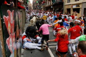 Garcigrande's fighting bulls run over revellers along the Curva de Estafeta during the fifth day of the San Fermin Running Of The Bulls festival on...