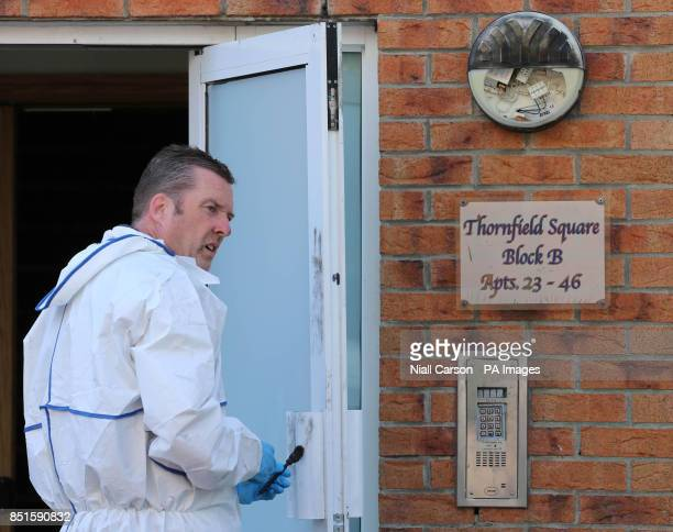 A Garda forensic officer dusts a door for fingerprints at the scene of a fire at an apartment complex in Watery Lane Clondalkin Dublin