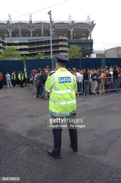 A Garda keeps watch over U2 fans queuing at the St James Avenue entrance to Croke Park stadium Diehard fans have been queuing all night for the best...
