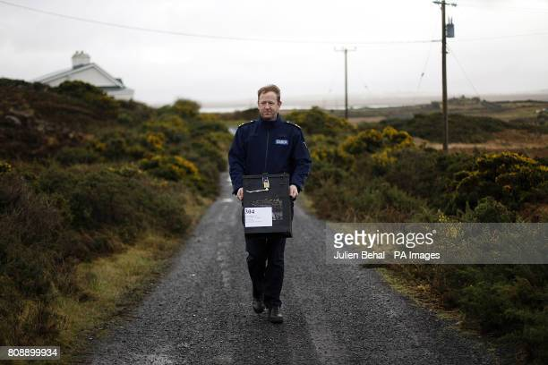 Garda Martin Reilly from Achill arrives with the balot box at the polling station in Scoil Mhuire on Inishbiggle a small inhabited island off the...