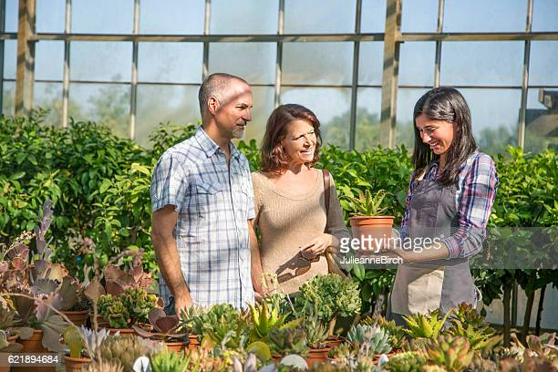 Garden center assistant helping customer