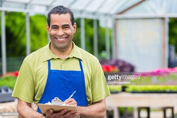 Garden center employee checks inventory in greenhouse