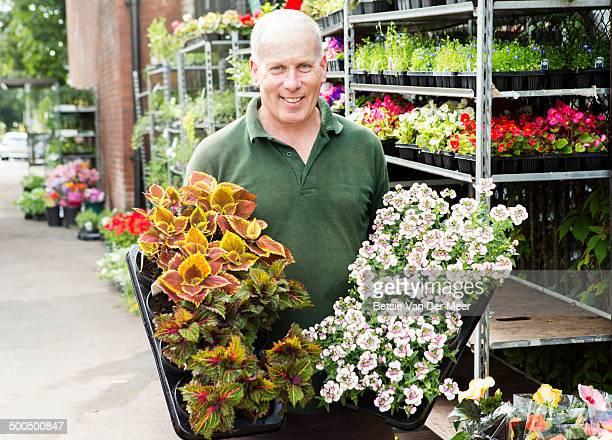 Garden center owner moving plants.