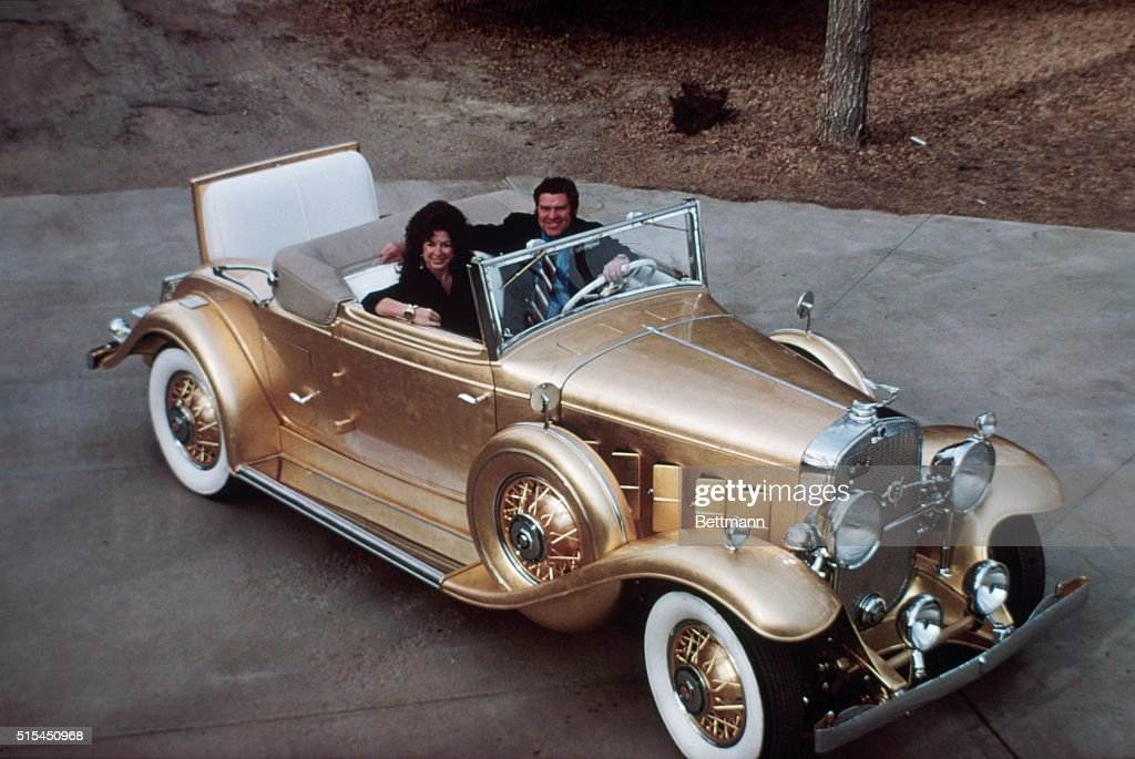 3/17/1975- Garden City, KS- Mr. and Mrs. Jack Smith sit in their 1931 'golden' Cadillac. It's not painted on--the entire car is done in 23.75 caret gold foil. Smith has restored many cars and this time he wanted something different. Smith spent three years turning his car into a 'golden oldie' and it is now valued at $500,000. The outside door handles are sterling silver, inside handles are 24 caret gold, and the gearshift knob is platinum set with 18 rare gems.
