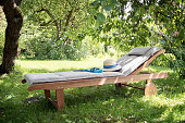 garden daybed made of wood with hat and sunglasses on a sunny meadow in the orchard, enjoy leisure in nature