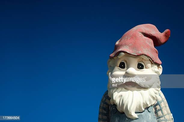 Garden gnome with red hat on a blue background