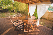 Relaxing home garden lounge with bamboo tree environment. Lantern on wooden table. Back deck.