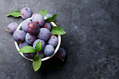 Garden plums in bowl on stone table. Top view with copy space for your text