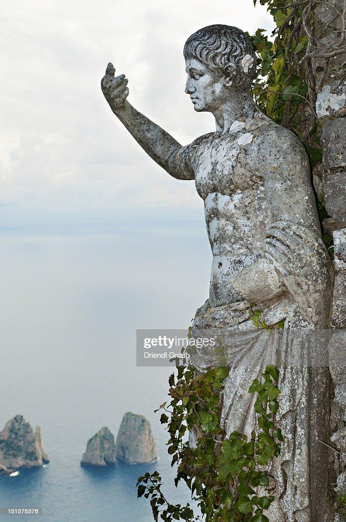 A garden statue and the Faraglioni. : Stock Photo