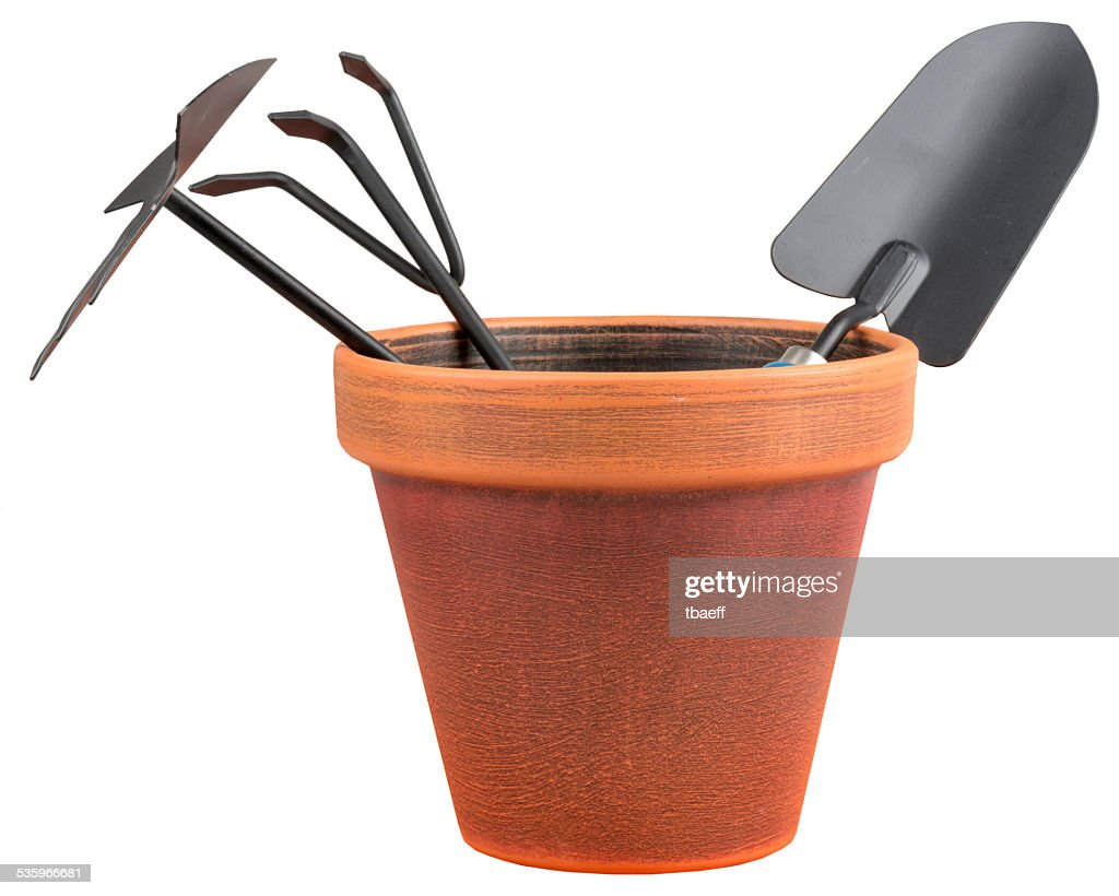 Garden tools in a orange vase : Stock Photo