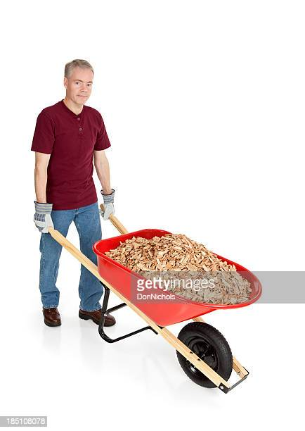 Gardener moving a Wheelbarrow Full of Mulch