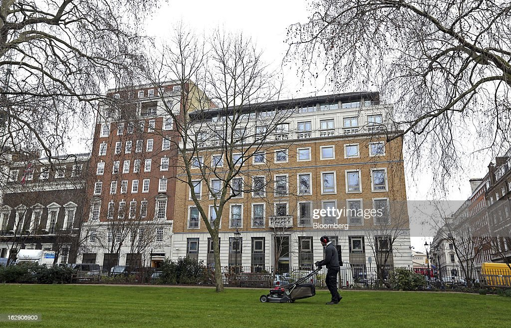 A gardener mows the lawn in St James's Square against a backdrop of BP Plc's headquarters in London, U.K., on Thursday, Feb. 28, 2013. BP Plc's push to maximize profits and cut costs at the Macondo well was a 'root cause' of the explosion that led to the 2010 Gulf of Mexico oil spill, a safety expert who studied the disaster said. Photographer: Chris Ratcliffe/Bloomberg via Getty Images