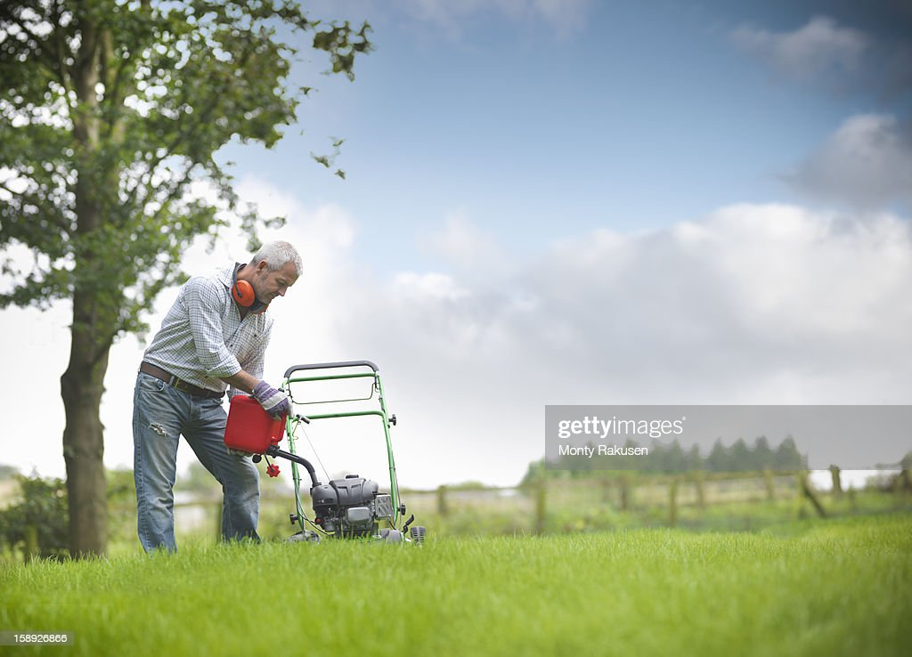 Gardener pouring petrol into lawn mower